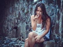 有香烟的可怜的少妇 库存照片