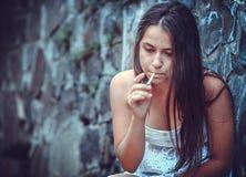 有香烟的可怜的少妇 库存图片