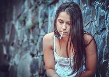 有香烟的可怜的少妇 免版税库存照片