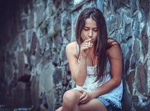 有香烟的可怜的少妇 免版税图库摄影