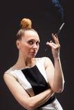 有香烟的可爱的年轻妇女 库存图片