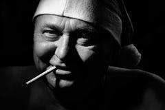 有香烟的坏圣诞老人 库存图片