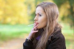 有香烟的女孩 免版税图库摄影