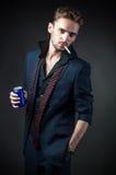 有香烟的性感的人和在罐子的一份饮料 免版税库存图片