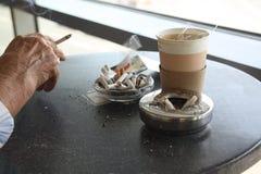 有香烟的手 免版税库存图片