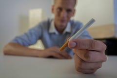 有香烟的英俊的人 免版税图库摄影