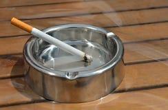 有香烟的金属烟灰缸 库存照片