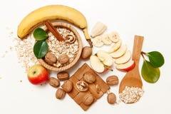有香蕉,苹果计算机,橙色用核桃在木板材和燕麦片,木匙子, Trivet,与绿色叶子,健康新鲜 免版税图库摄影