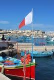 有马尔他旗子的五颜六色的渔船在Marsaxlokk,马耳他 库存照片