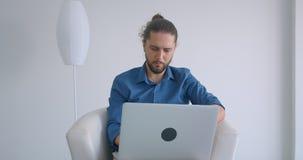 有马尾辫工作的进步自由职业者与坐在扶手椅子的膝上型计算机在舒适和轻的办公室 股票视频