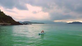 有马尾辫的女孩在paddleboard的姿势站立在海洋 股票视频