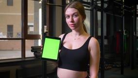 有马尾辫的女运动员显示有chromakey绿色屏幕的片剂入是镇静的和微笑在健身房的照相机, 影视素材