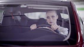 有马尾辫的年轻女人在红色汽车坐,闭上在方向盘后的眼睛 股票视频