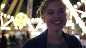 有马尾辫的年轻美丽的愉快的女孩微笑和看照相机的特写镜头观点的停留在游乐园 影视素材
