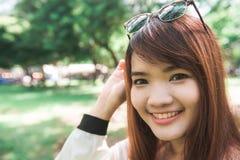 有马尾辫的镇静美丽的微笑的少妇享用新鲜空气的室外 图库摄影