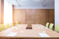 有马掌棕色木桌的办公室室和腼腆的绿色椅子 免版税库存图片