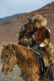 有马的年轻哈萨克人老鹰女猎人Berkutchi妇女,当寻找对与的野兔在他的胳膊时的鹫 库存图片