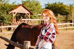 有马的快乐的可爱的少妇女牛仔在村庄 免版税库存图片