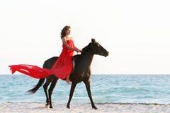 有马的愉快的妇女在海运背景 免版税库存图片