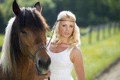 有马的白肤金发的女孩 库存图片