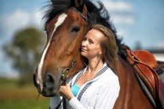 有马的白肤金发的妇女 免版税库存照片