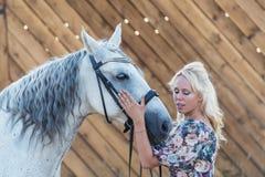 有马的美丽的白肤金发的妇女 库存图片