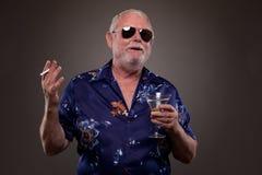 有马蒂尼鸡尾酒和香烟的愉快的人 库存照片