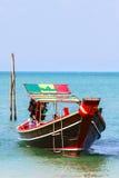 有马达和一个多彩多姿的屋顶的木小船 免版税库存照片