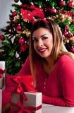 有驯鹿垫铁的女孩在顶头和红色毛线衣和礼物盒,圣诞树在背景中 库存图片