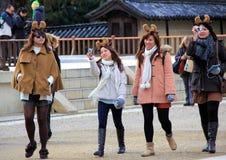 有驯鹿垫铁的时兴的日本妇女在他们的头 免版税库存照片