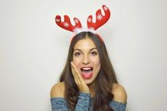 有驯鹿垫铁的美丽的惊奇的圣诞节女孩在她的头有灰色背景 免版税库存照片
