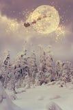 有驯鹿飞行的圣诞老人通过天空 库存图片