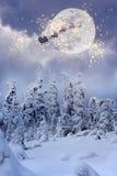 有驯鹿飞行的圣诞老人通过天空 免版税库存照片
