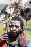 有驼鸟的非洲孩子用羽毛装饰头饰和面孔被绘的标号  库存图片