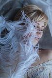 有驼鸟羽毛的美丽的妇女  库存照片