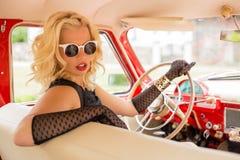 有驾驶一辆减速火箭的汽车的太阳镜的妇女 免版税库存图片