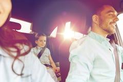 有驾驶在汽车的小孩的愉快的家庭 图库摄影