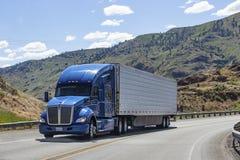 有驾驶在高速公路的拖车的半卡车 免版税库存图片