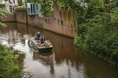 有驾驶运河的人的小船围拢由墙壁和豪华的植被在s斯海尔托亨博斯 免版税图库摄影