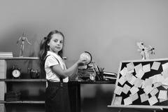 有骄傲的面孔的女小学生在她的手上拿着一点地球 免版税库存照片