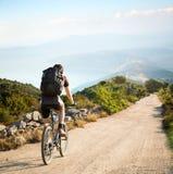 有骑在山的背包的人一辆自行车 库存照片