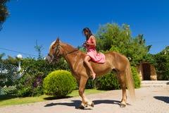 有骑她棕色白肤金发的马的红色礼服的年轻浅黑肤色的男人 免版税库存图片