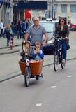 有骑自行车的两个孩子的父亲 库存照片