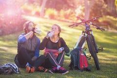有骑自行车的人的夫妇放松和水 库存照片