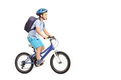 有骑自行车的盔甲的男小学生 库存图片