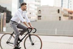 有骑自行车的耳机的人在城市街道 免版税库存图片