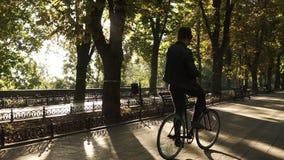 有骑自行车的耳机的年轻人在公园在迁徙的黑自行车 乘坐和跳舞,当听时 股票视频