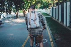 有骑自行车的背包的年轻人通过植物公园,背面图,每日生活方式都市休息的概念 免版税库存照片