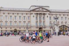 有骑自行车者人群的白金汉宫在以前它前面的 免版税图库摄影