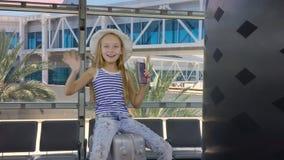 有骑马的快乐的女孩在手提箱,当等待在离开休息室在机场时 股票视频